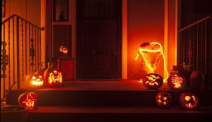 Carved pumpkins and other decorations sit outside a dark house on Halloween