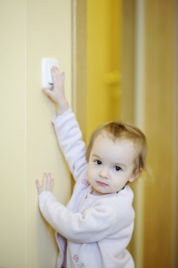 Adorable toddler girl turning off the light-switch